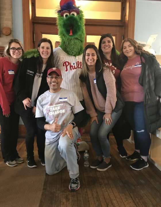 Kacie Ricciotti, Terra Kliwinski, Professor David W. Brown, Mary Strehl, Marissa Reale, Jennifer Lynch. Picture of teammates along with their professor and the Philly Phinatic, at the Play with Purpose event.